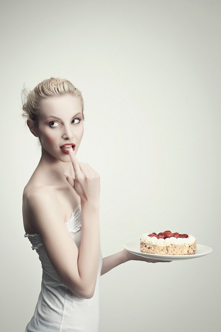 A young woman tasting cream from strawberry cake with her finger