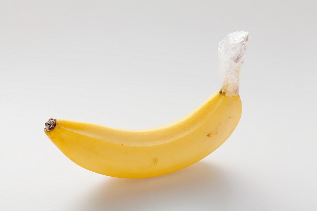 A banana with the stem wrapped in cling-film to keep it fresh for longer