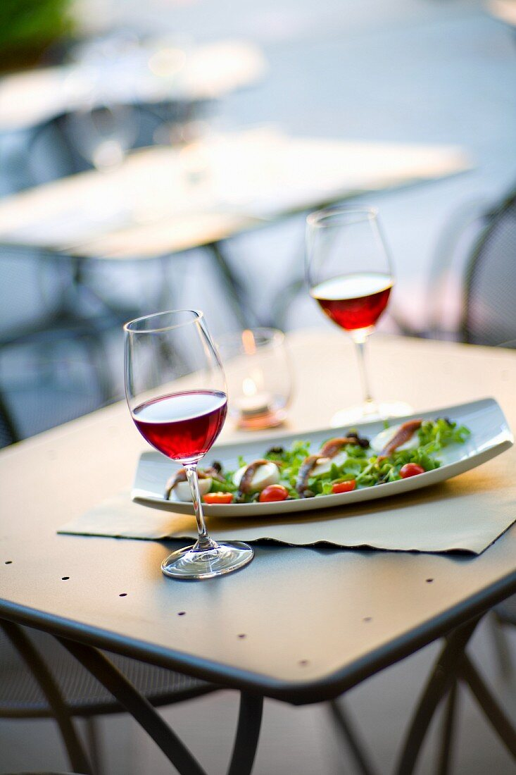 An aperitif of red wine with anchovy and mozzarella on salad leaves