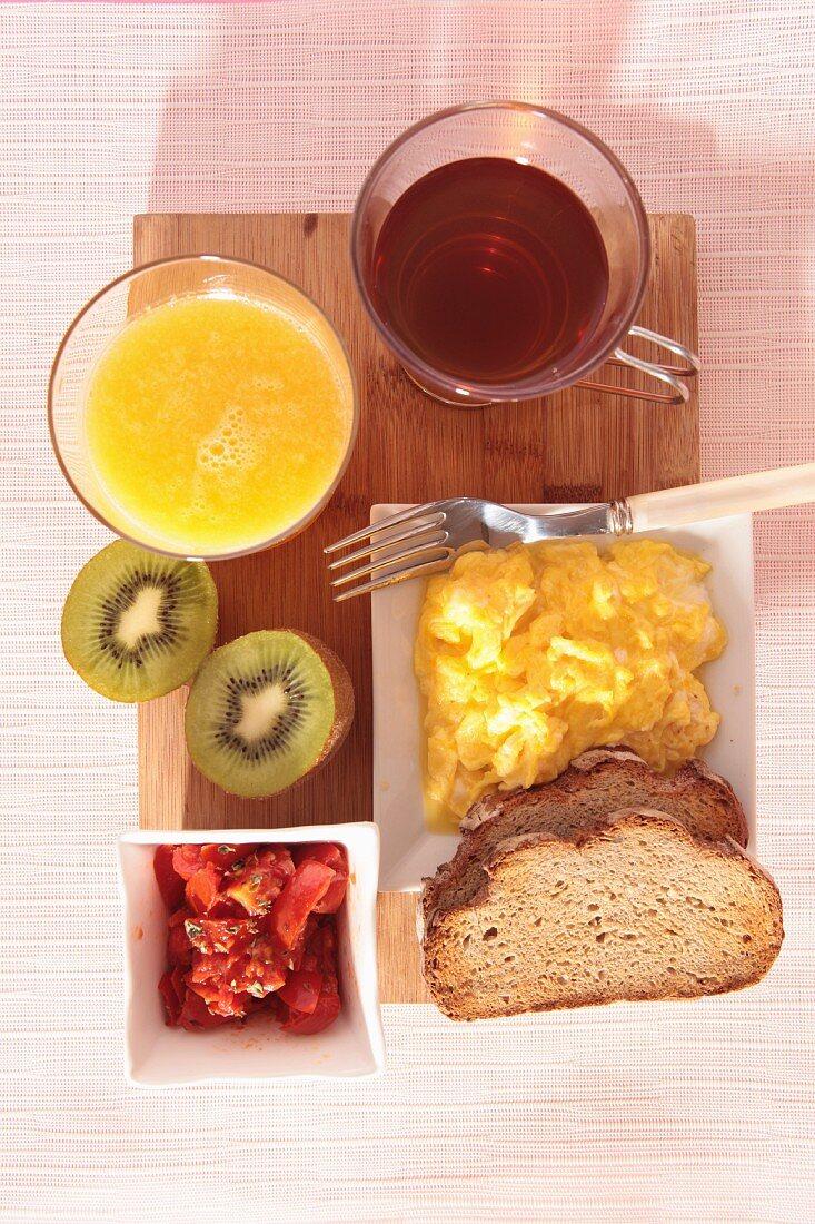 A breakfast of orange juice, tea, scrambled egg and fruit