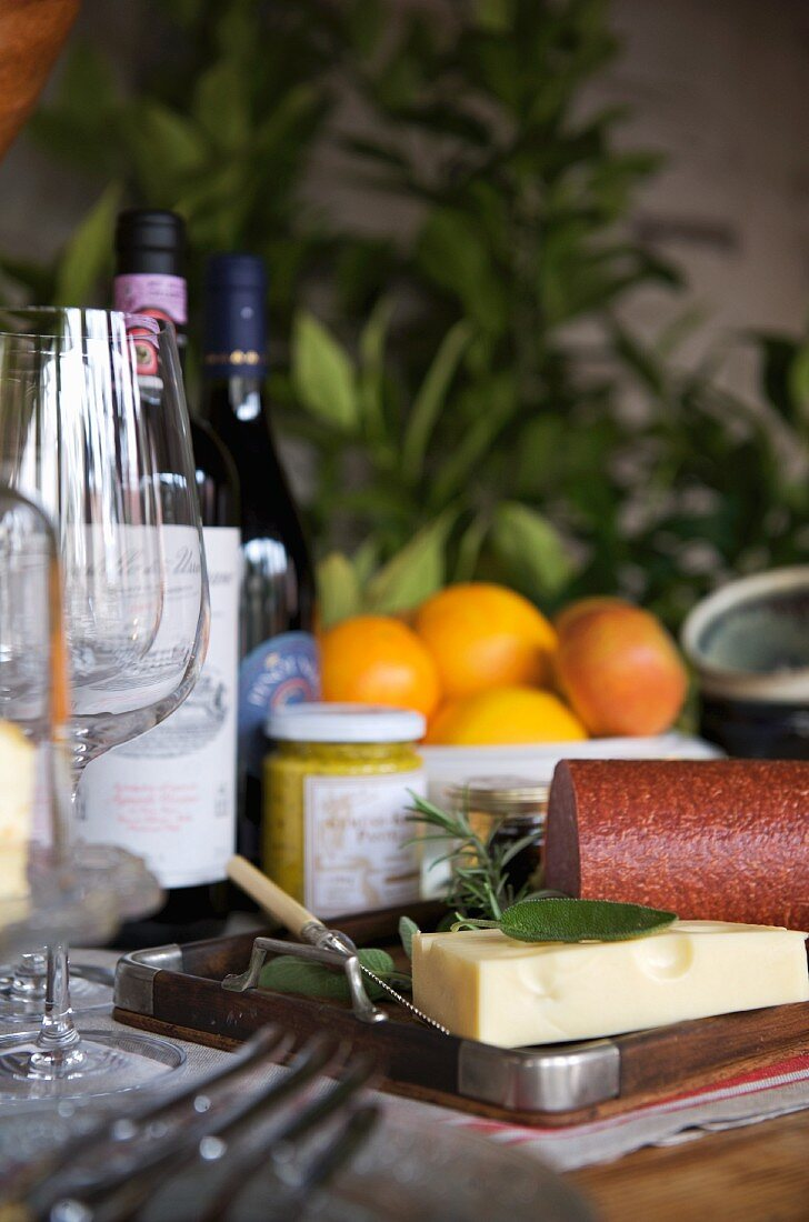 Still-life arrangement of wooden tray next to red wine glasses, bottles of wine, cheese, cold meat and jar of mustard; oranges and apples in fruit bowl in background