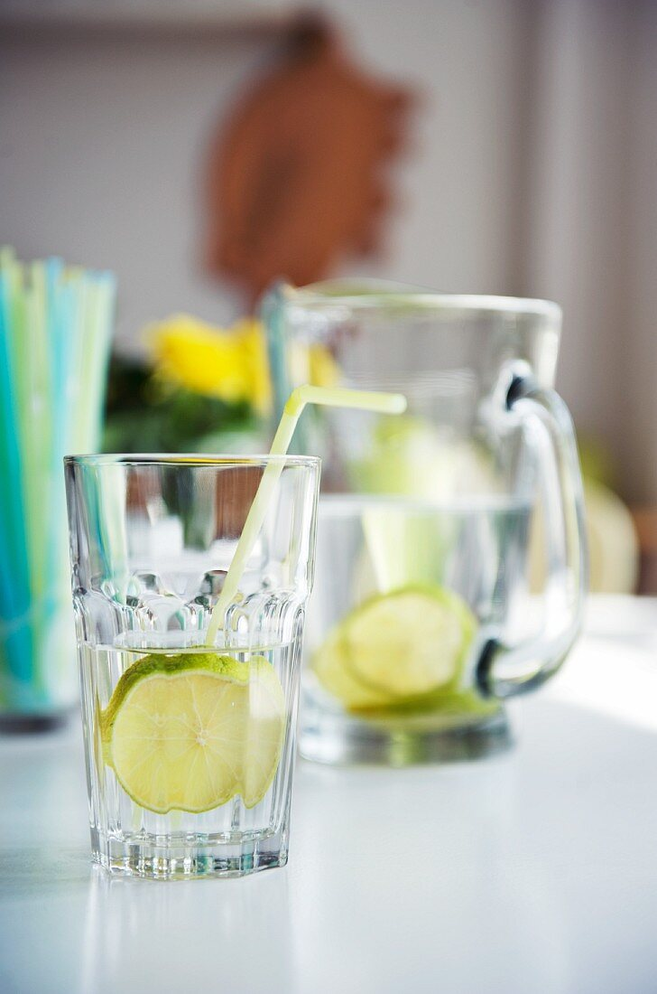 Glasses and jug of lemon water on white table