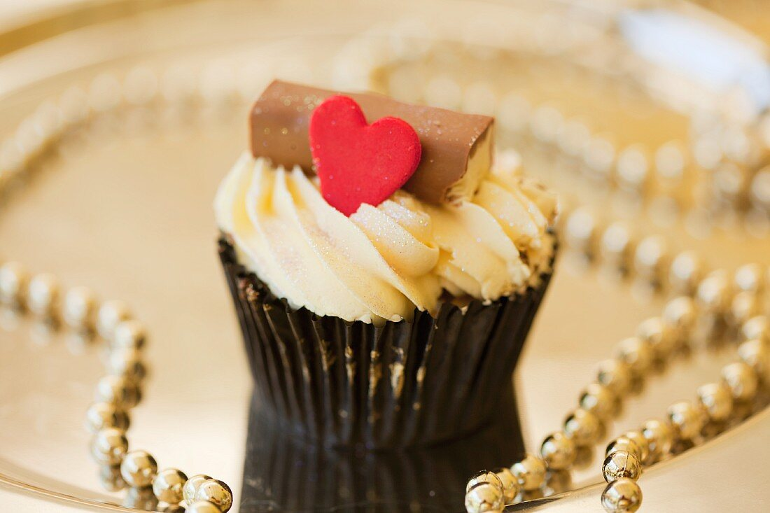 A cupcake on a gold plate with strings of pearls