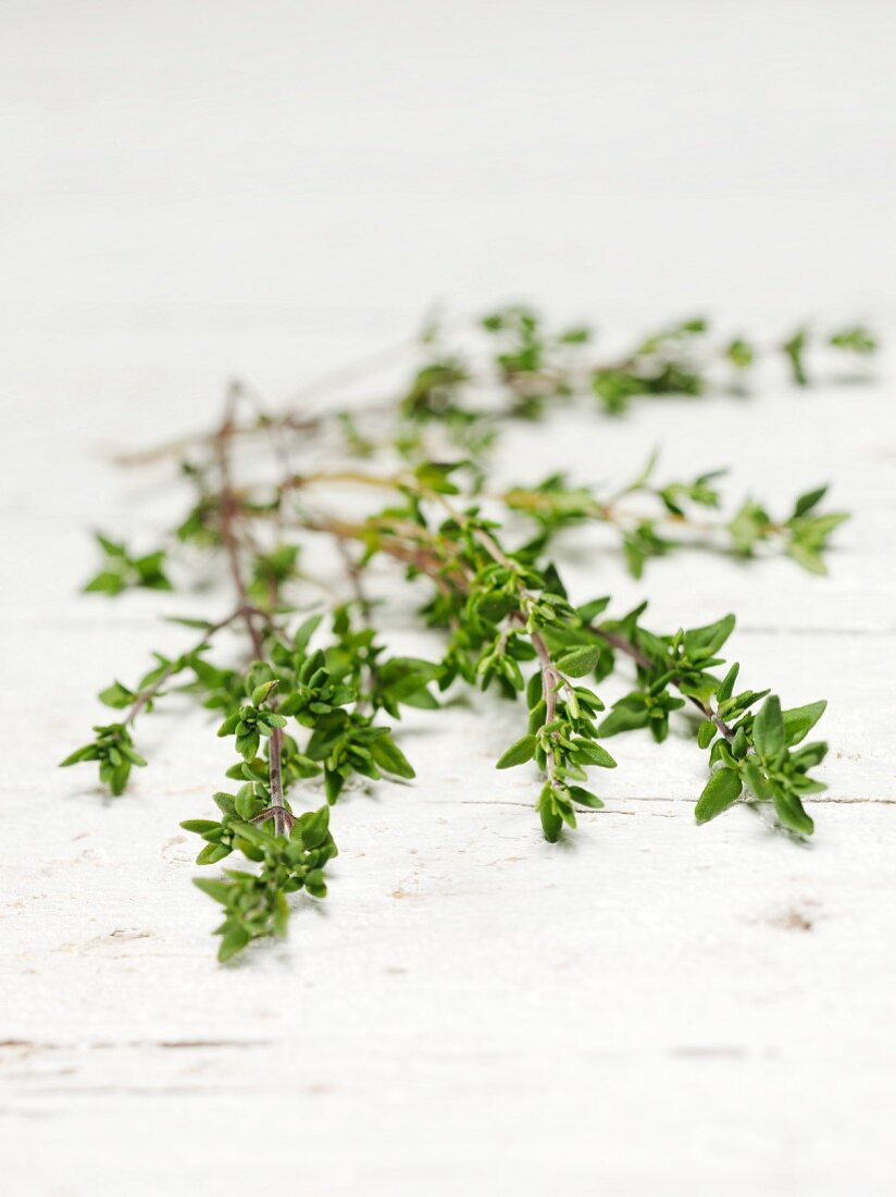 Sprigs of thyme on a white wooden table