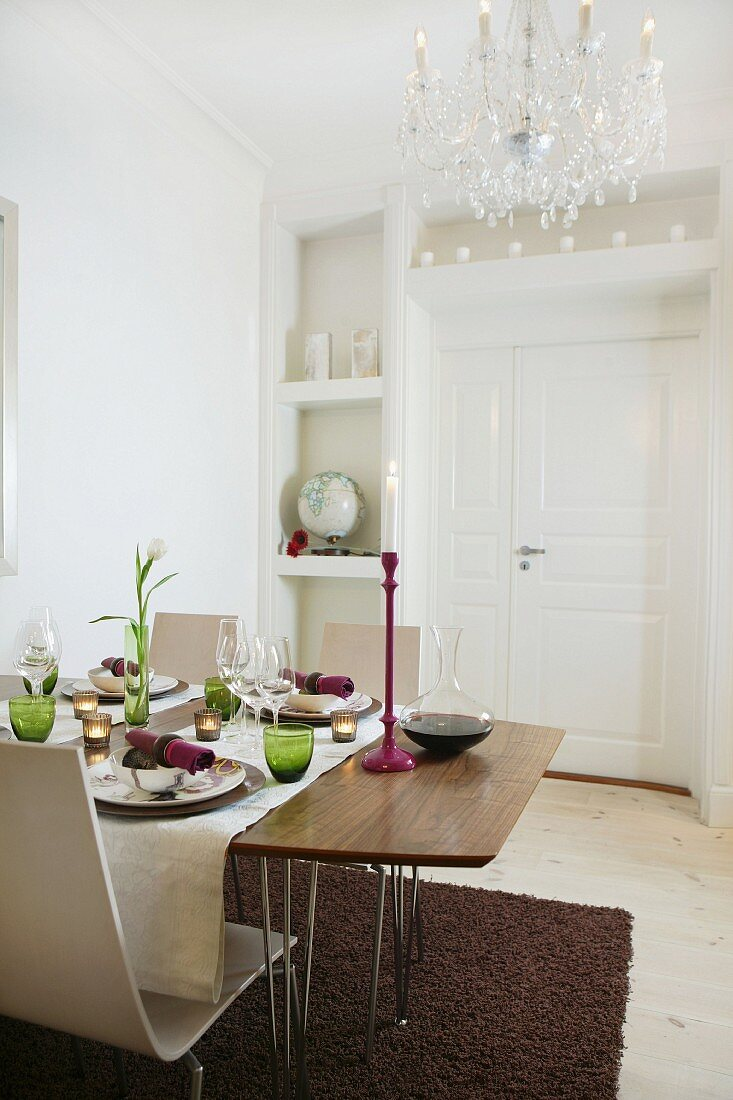 Set table in white dining room with traditional chandelier hanging from ceiling