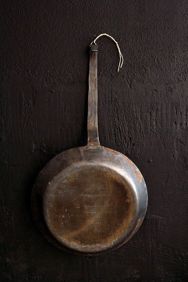 Vintage iron frying pan hanging on black wall
