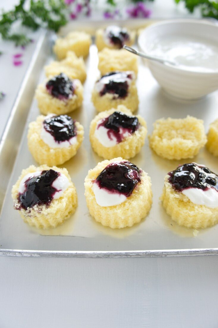 Little, fluted cut-out sponge cakes with bilberry jam