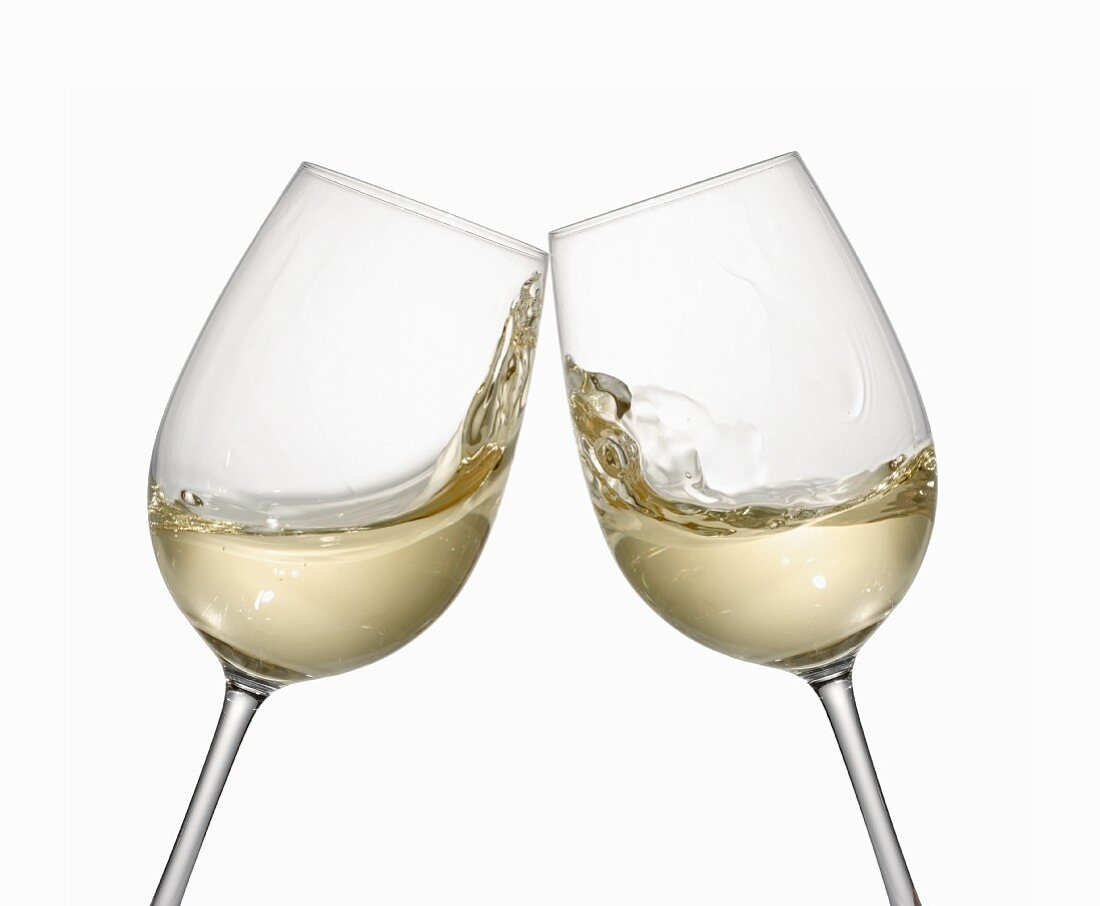 White wine glasses being clinked together