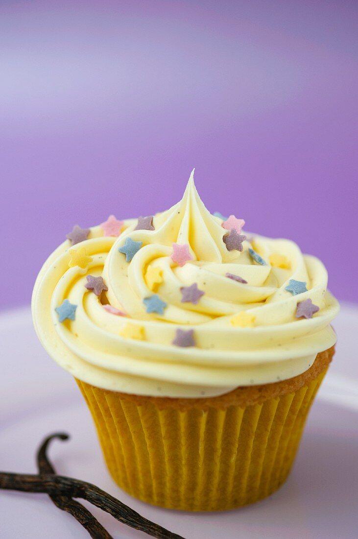 A vanilla cupcake with colourful sugar stars