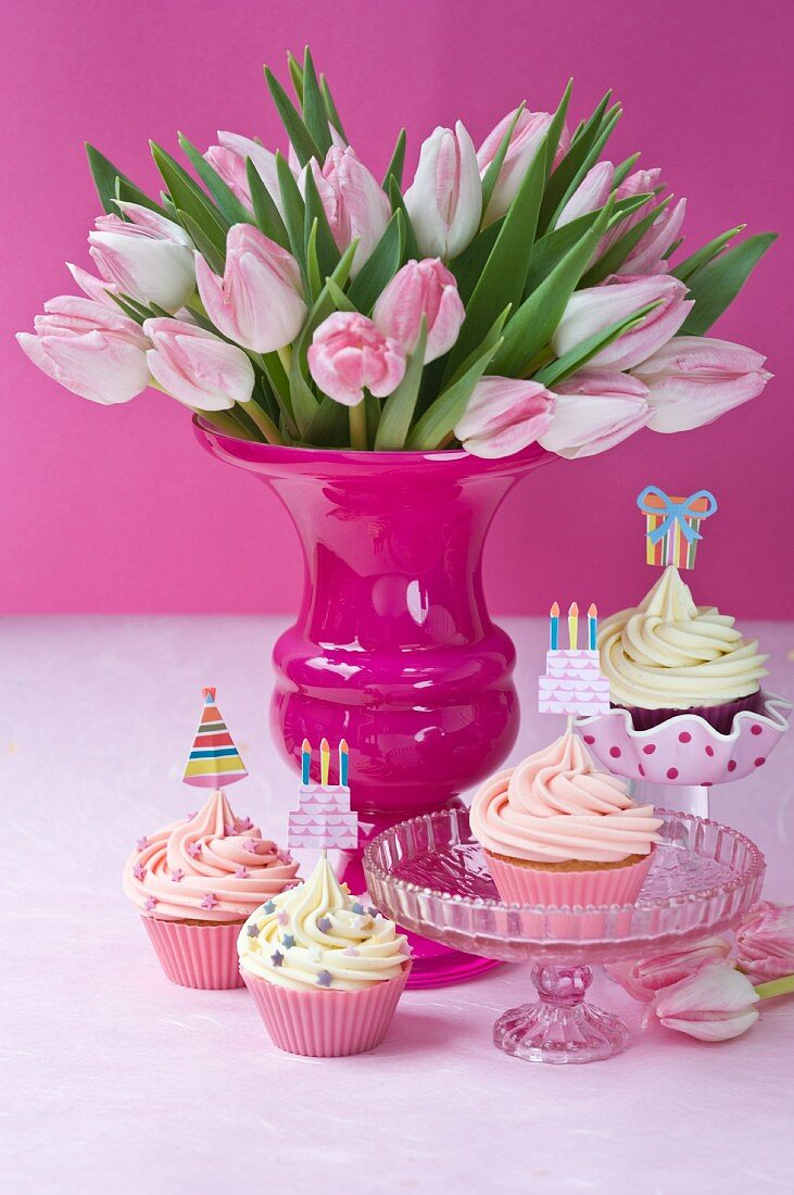 Cupcakes with party toppers and bouquet of tulips