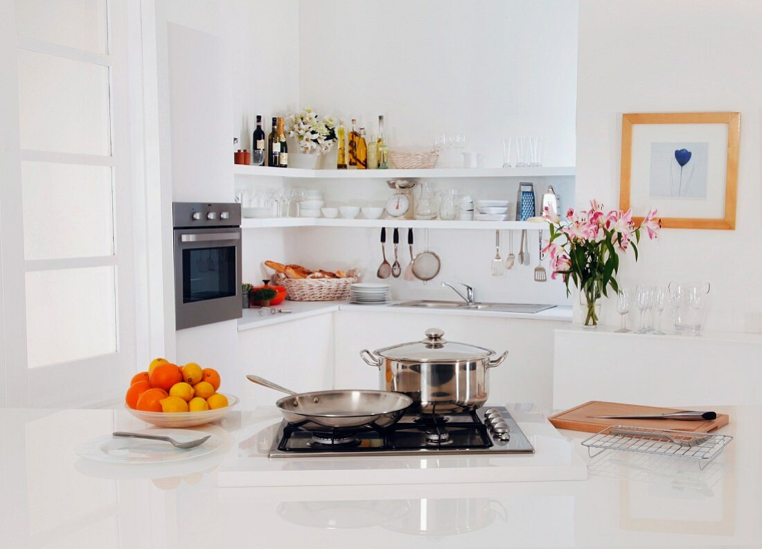 A contemporary white kitchen with a gas hob and various cooking utensils
