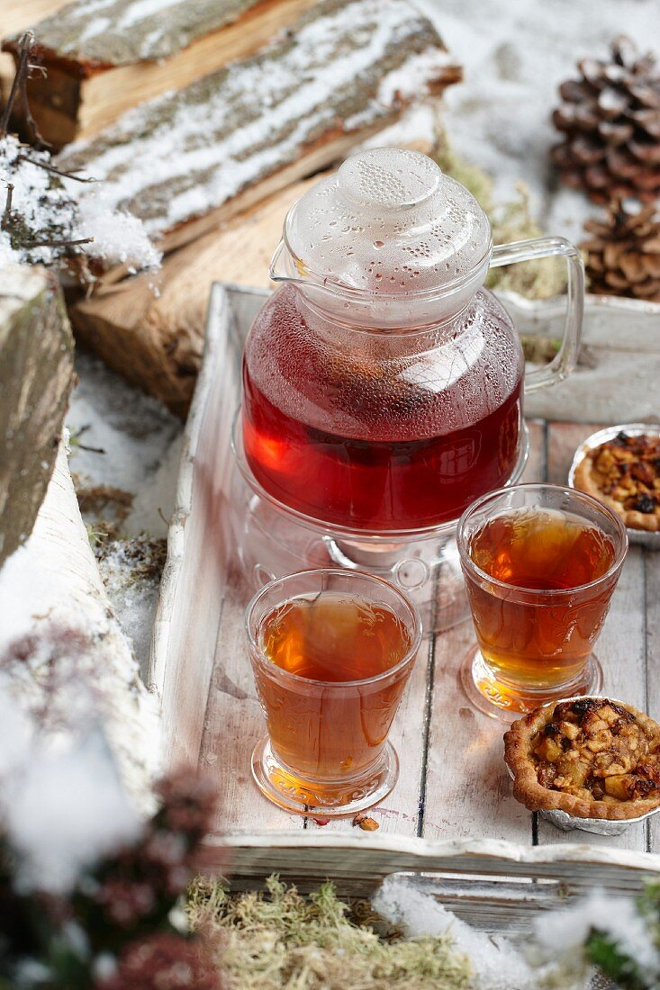 Winter tea and tartlets on a wooden tray in the snow