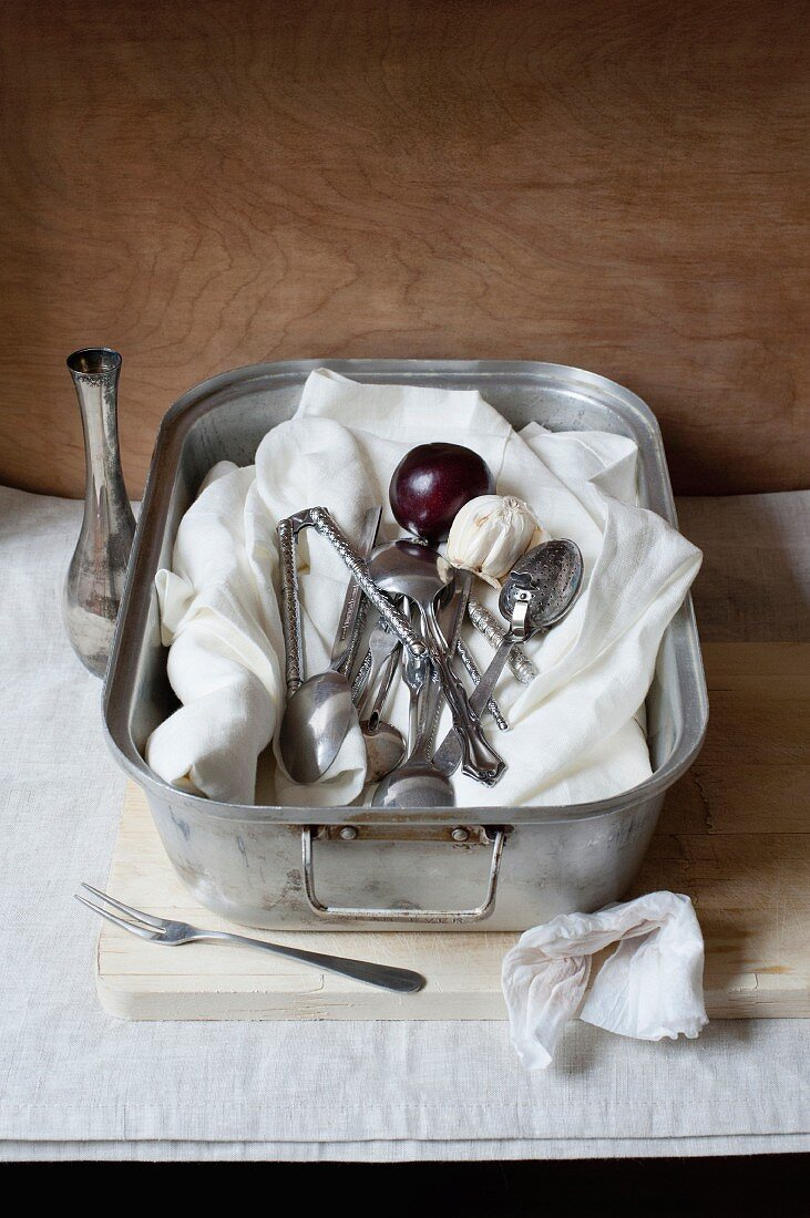Muslin cloth, kitchen utensils and plums in a roasting tin