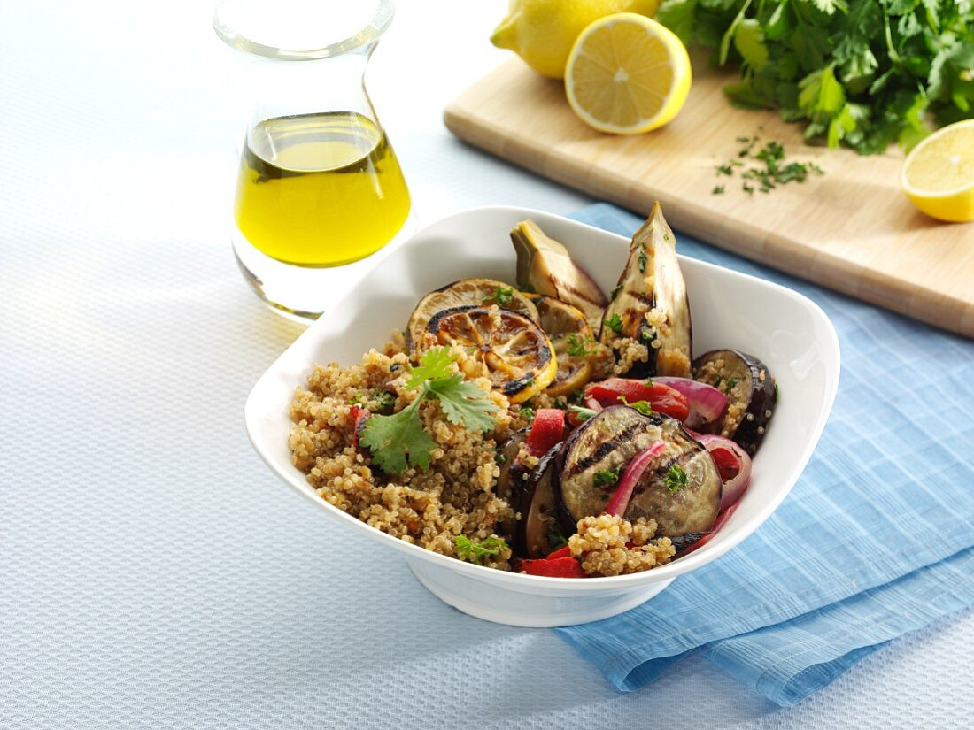 Warm Quinoa Salad with Grilled Eggplant , Red Onion and Lemon in a White Bowl; Olive Oil, Parsley and Lemons in Background
