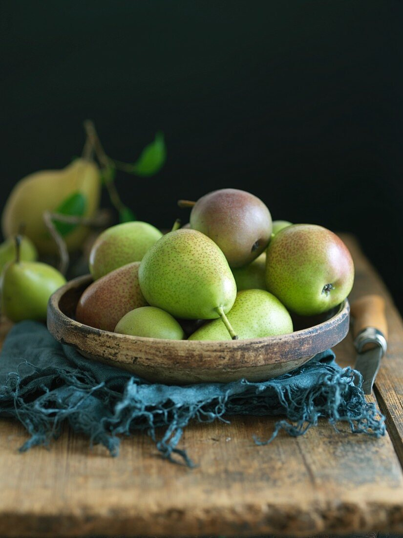 Forelle and Seckel Pears in a Wooden Bowl on a Rustic Wooden Table