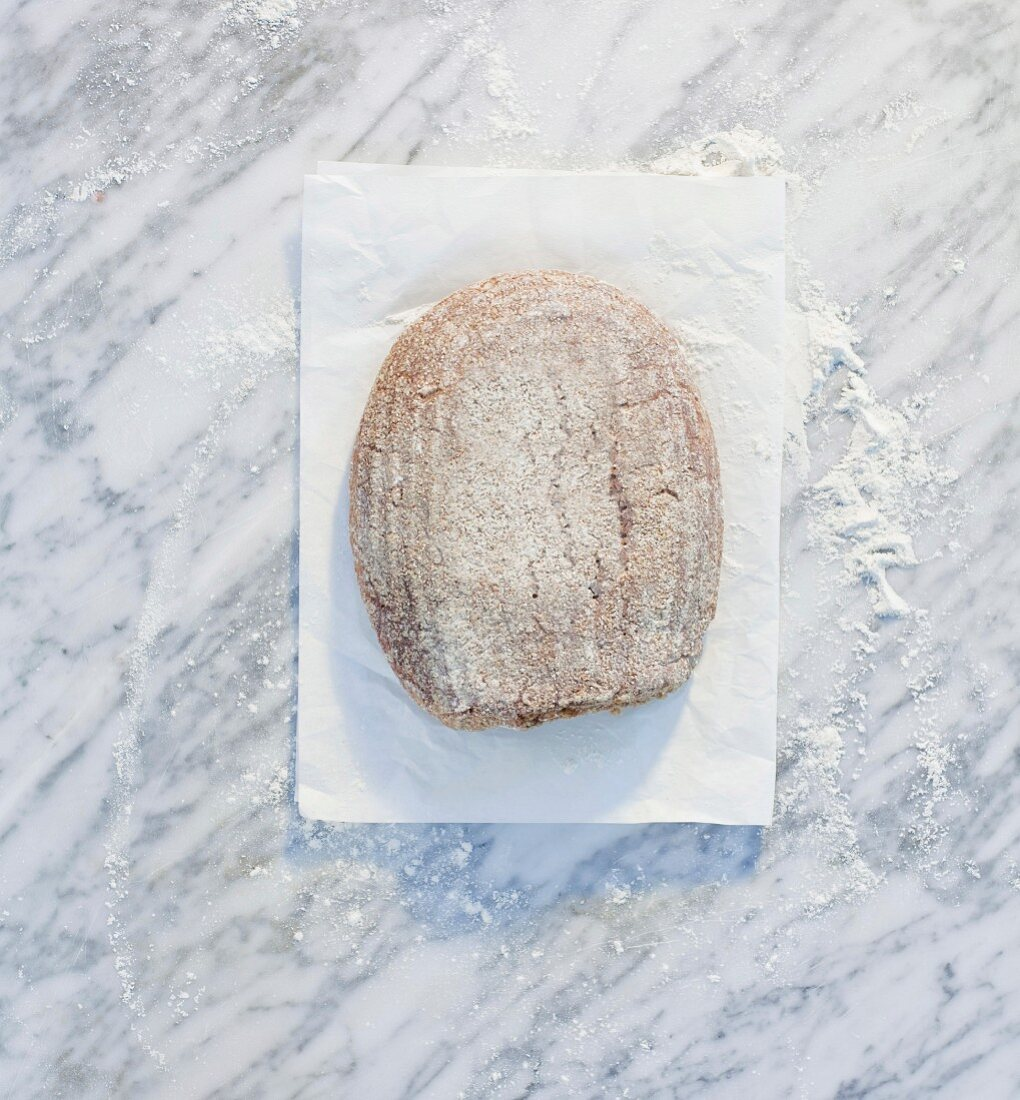A loaf of bread on paper, on a marble surface, dusted with flour