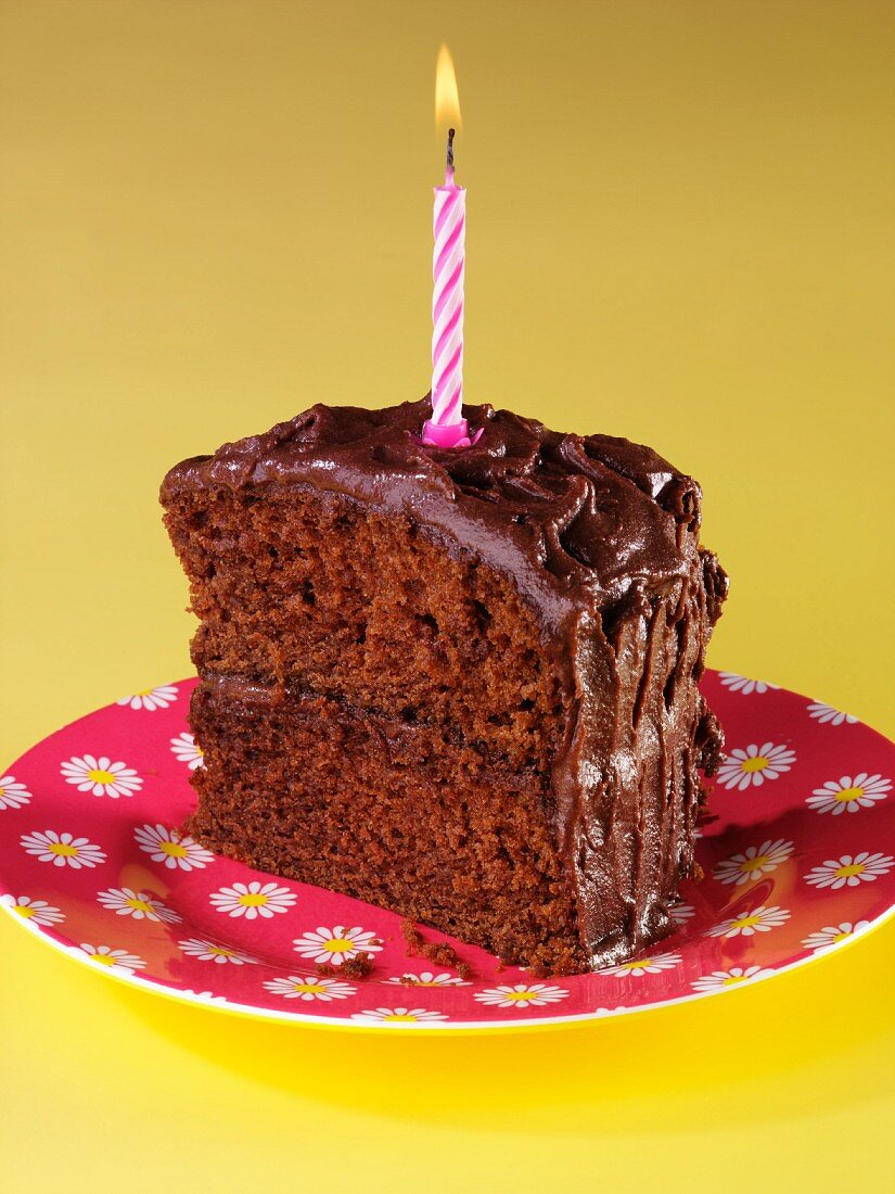 A slice of devil's food cake (chocolate layer cake, USA) with a birthday candle