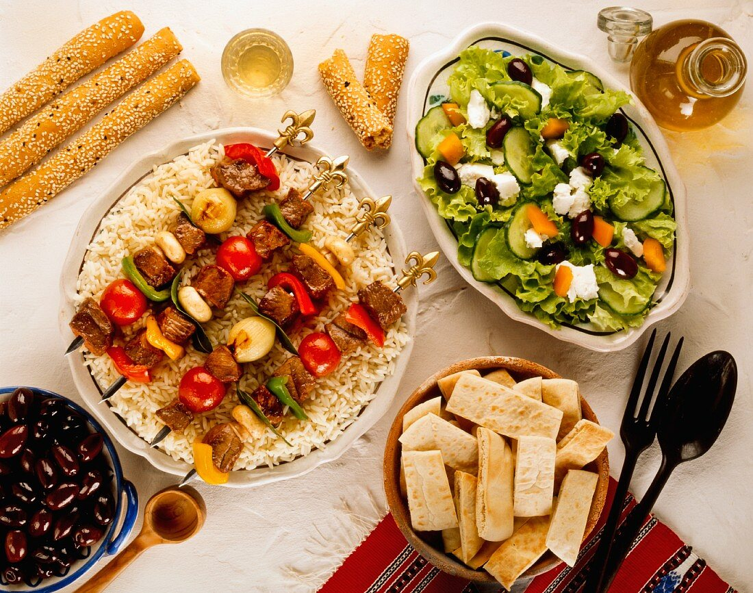 Grilled skewers of lamb on rice, with salad, pita bread and olives (Greece)