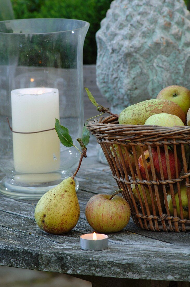 Basket of apples and pears on faded terrace table; large lantern in background