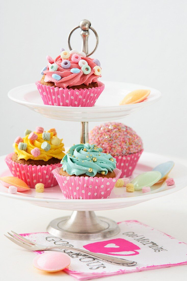 Cupcakes with different decorations on tiered stand