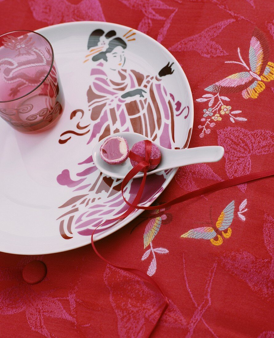 A porcelain plate with a geisha motif on an embroidered tablecloth