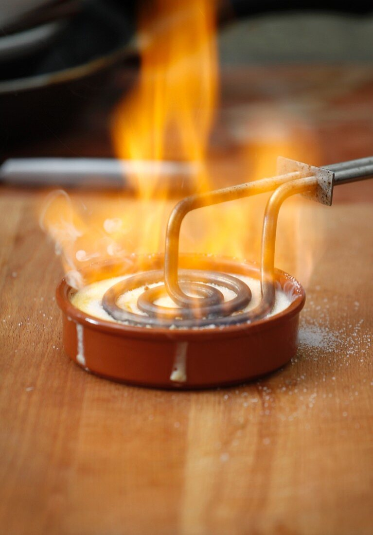 Crema catalana being caramelised with a branding iron