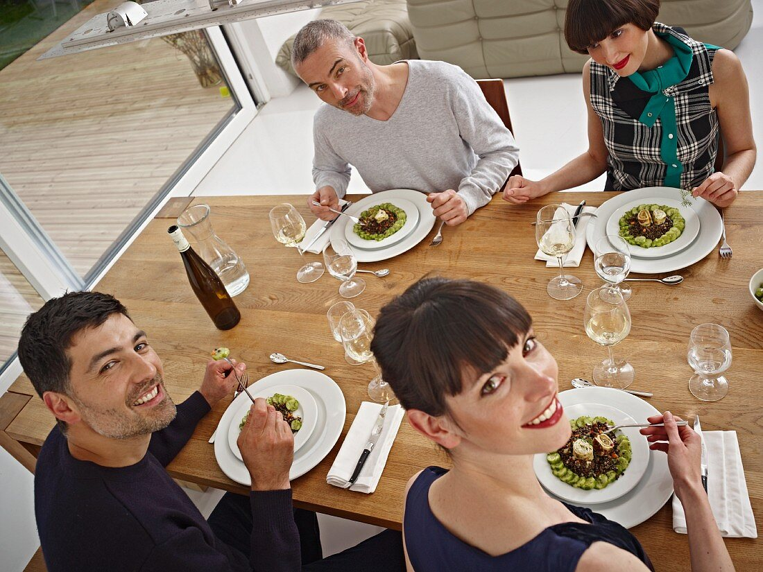 Two couples eating at home