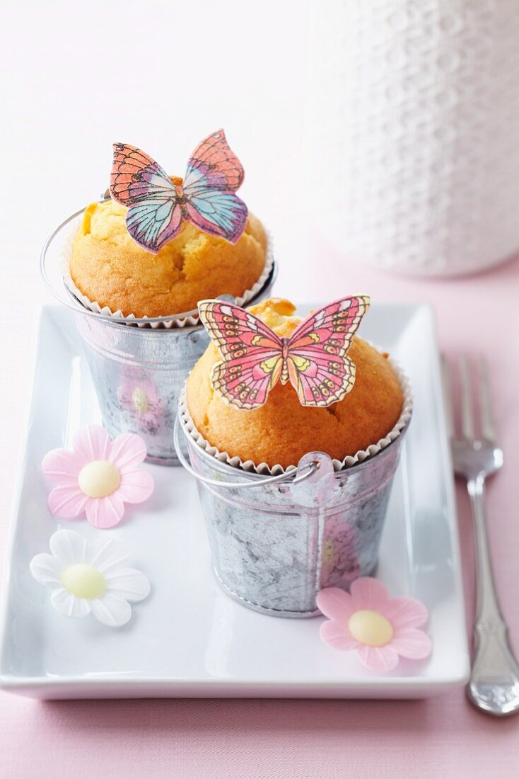 Muffins decorating with butterflies and flowers made from edible paper