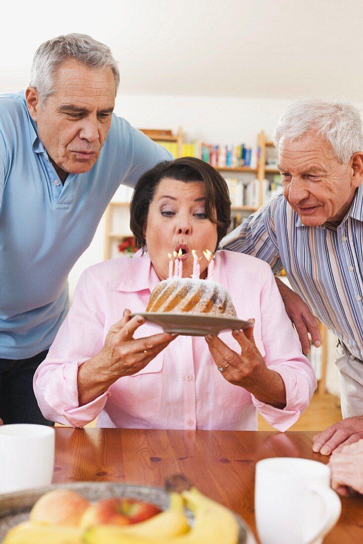Ältere Männer und Frau blasen die Kerzen auf dem Geburtstagskuchen aus