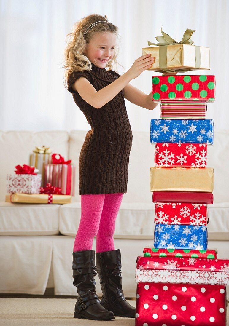 Young girl stacking Christmas gifts