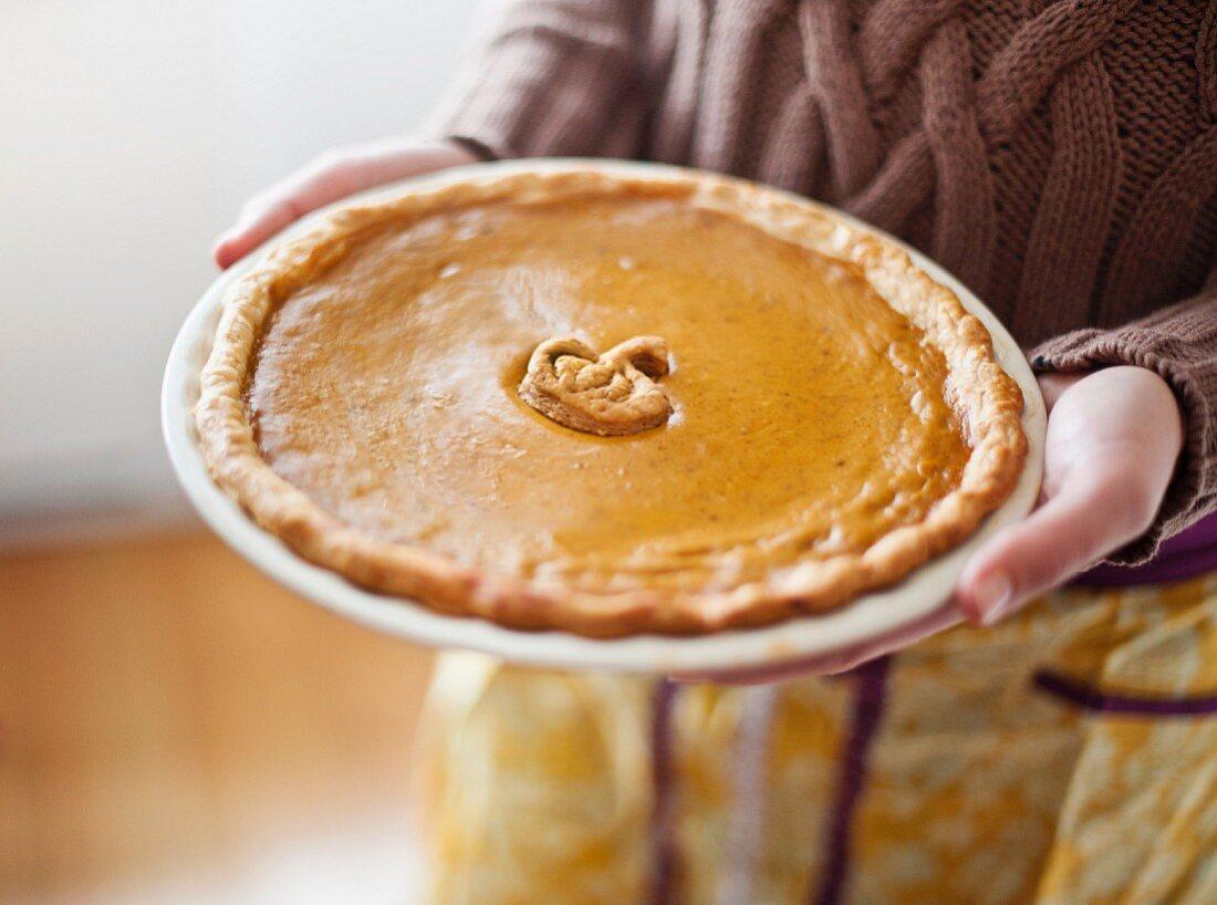 Close up of woman holding pumpkin pie
