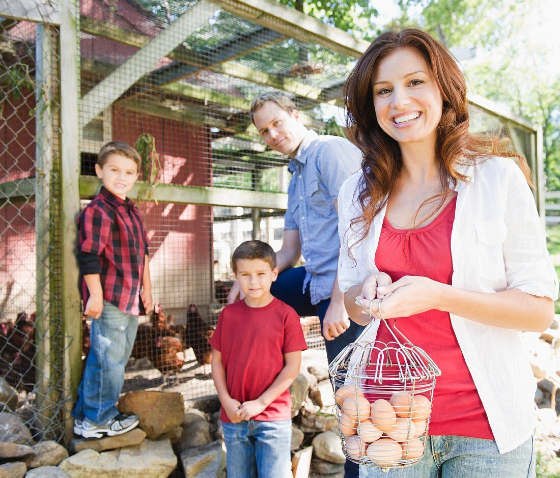 USA, New York, Flanders, Family with two boys (4-5, 8-9) picking up eggs from hen house