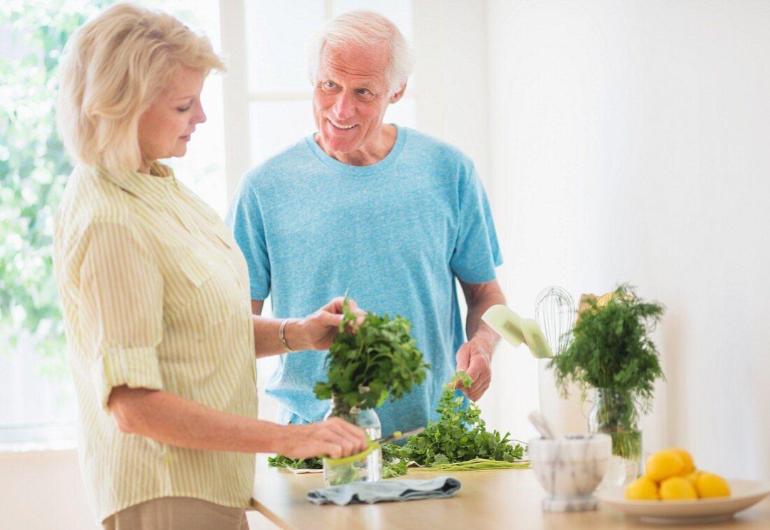Älteres Paar bereitet Kräuter in der Küche vor