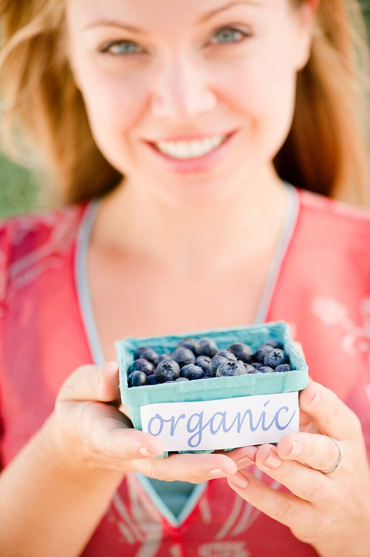 USA, New Jersey, Jersey City, Young attractive woman offering box of blueberries