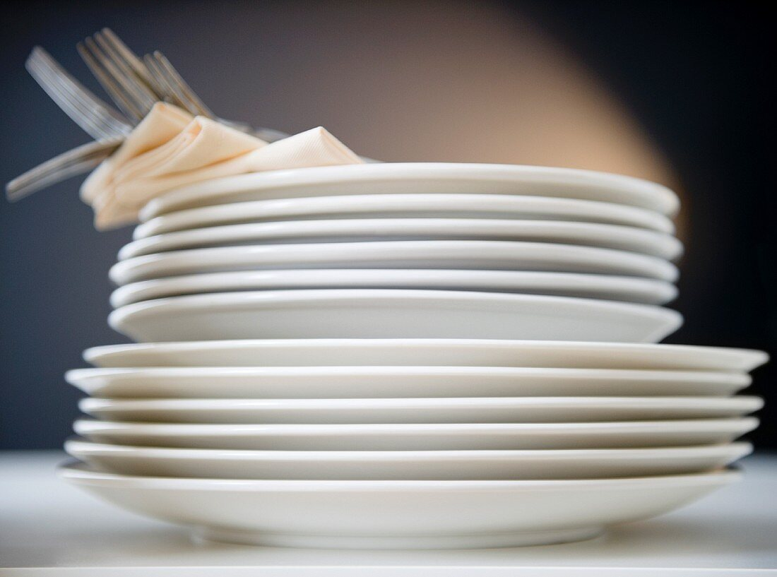 Stack of plates and forks, studio shot