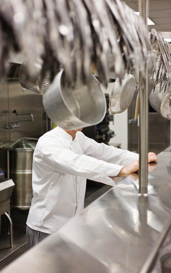 Koch hinter hängendem Kochgeschirr versteckt