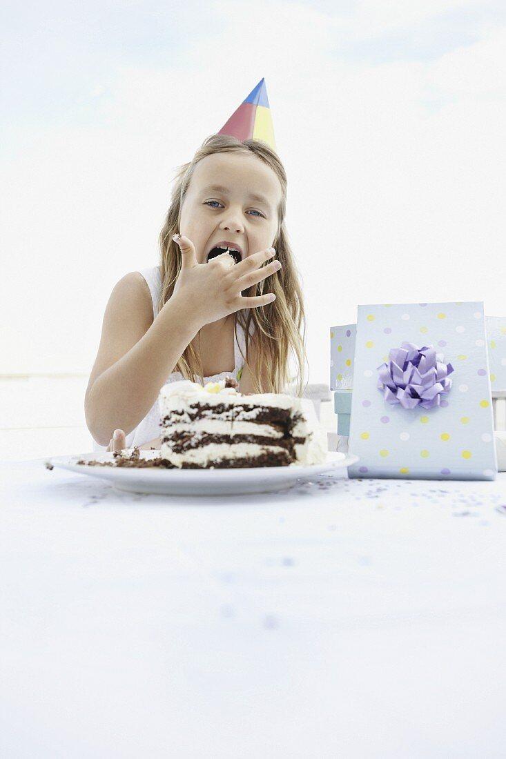 Young girl eating birthday cake