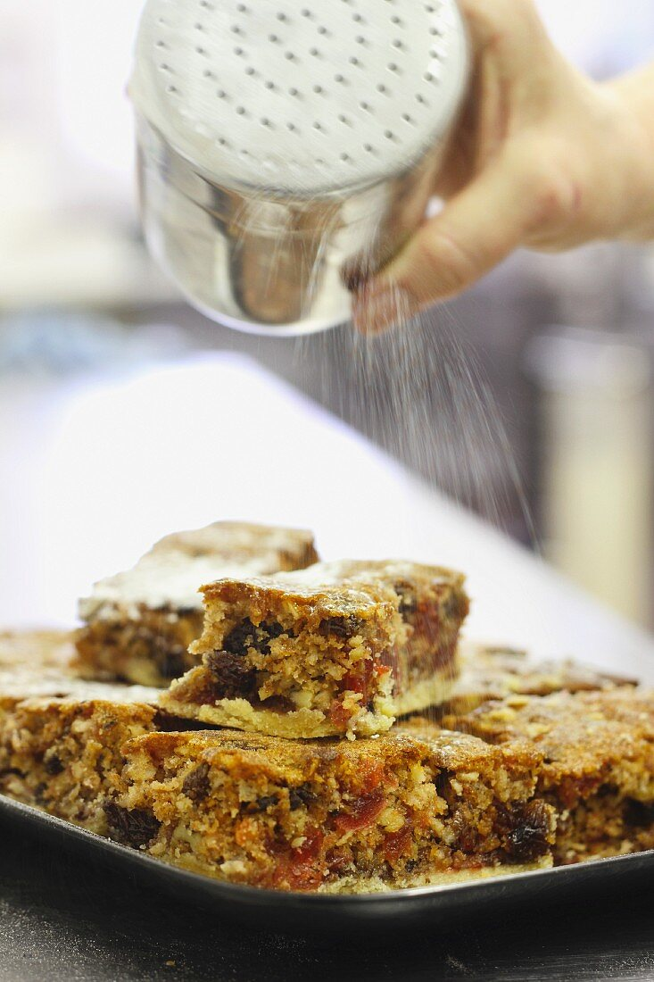 Dusting fruit cakes with powdered sugar