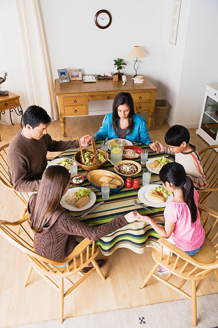 Family with three children (8-9, 10-11) praying at table