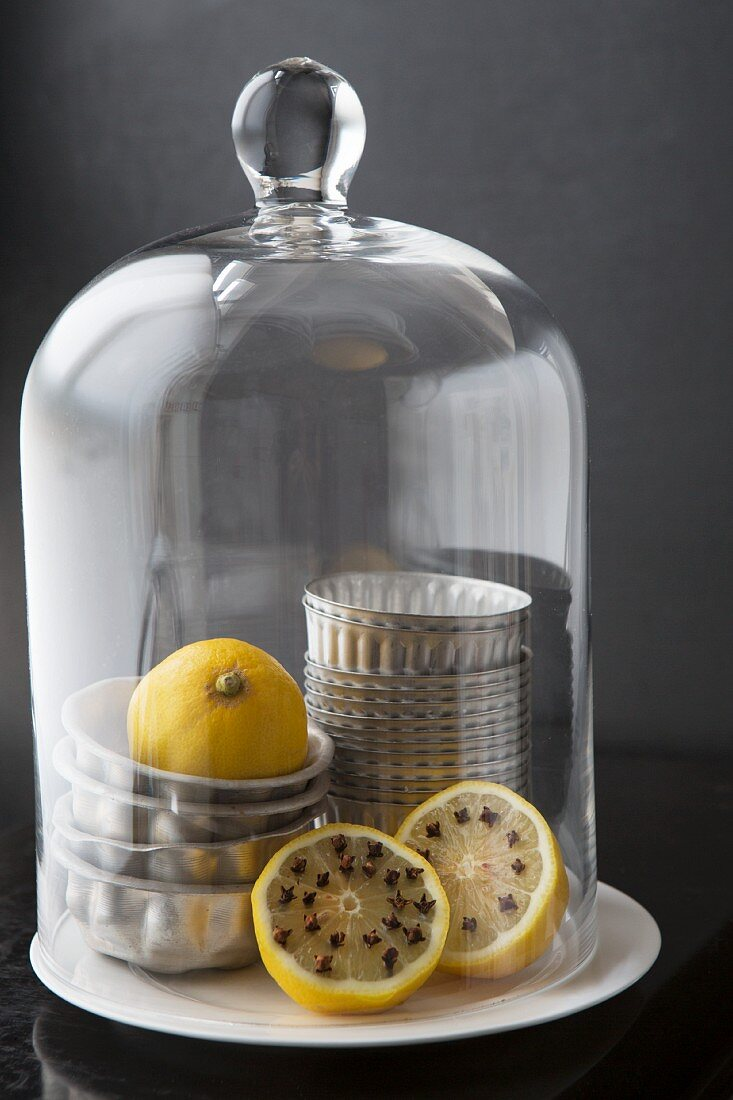 Lemons studded with cloves and muffin tins under a domed glass cover