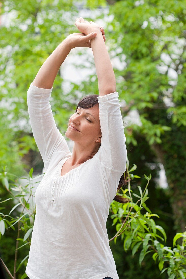 Women with stretching with arms overhead in the garden