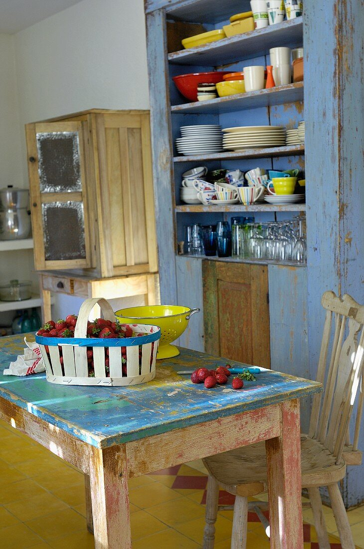 Vintage kitchen - punnet of strawberries on table with peeling paint in front of crockery in rustic kitchen dresser