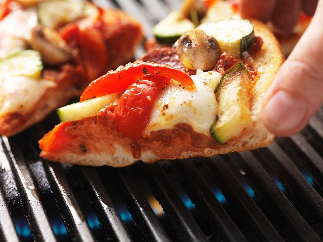 A hand reaching for a slice of pizza on the barbecue