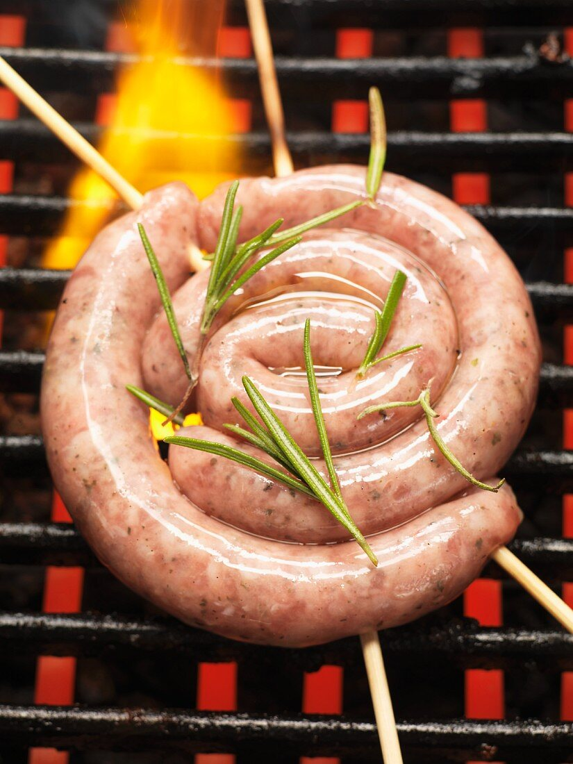 Raw sausage spiral with rosemary on the barbecue