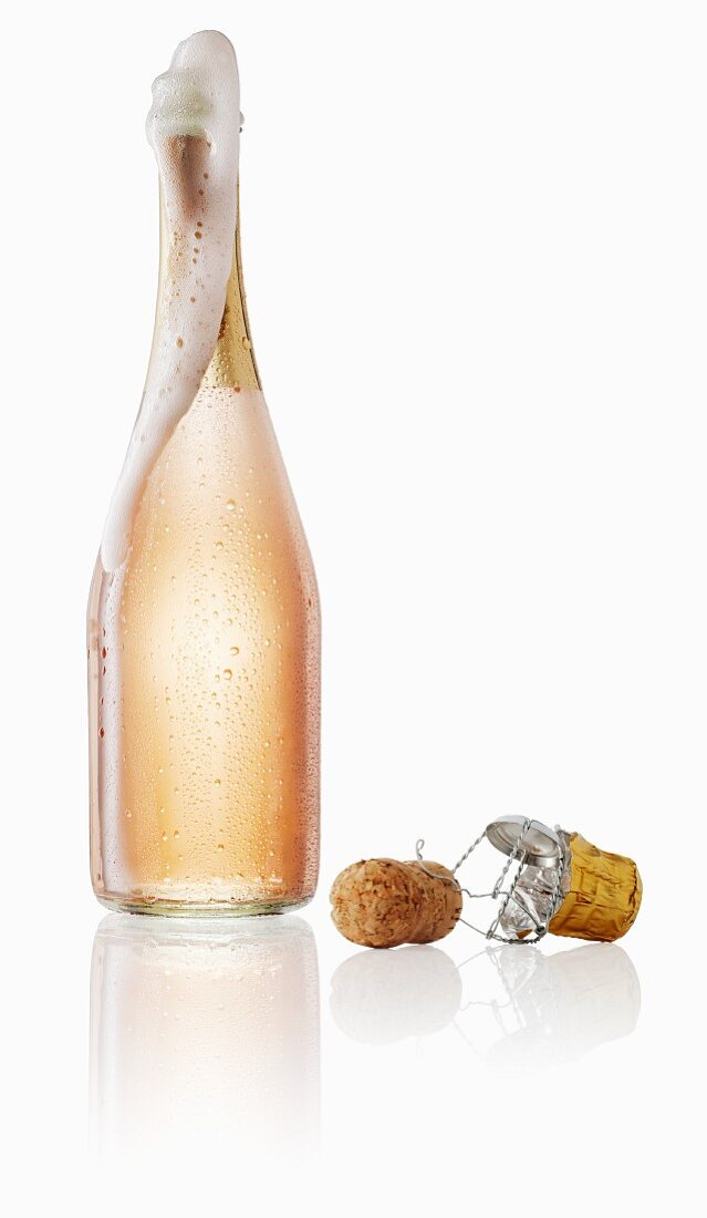 Pink champagne bubbling out the bottle