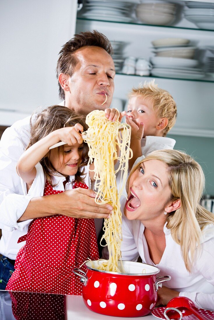 Germany, Family playing with spaghetti on kitchen worktop