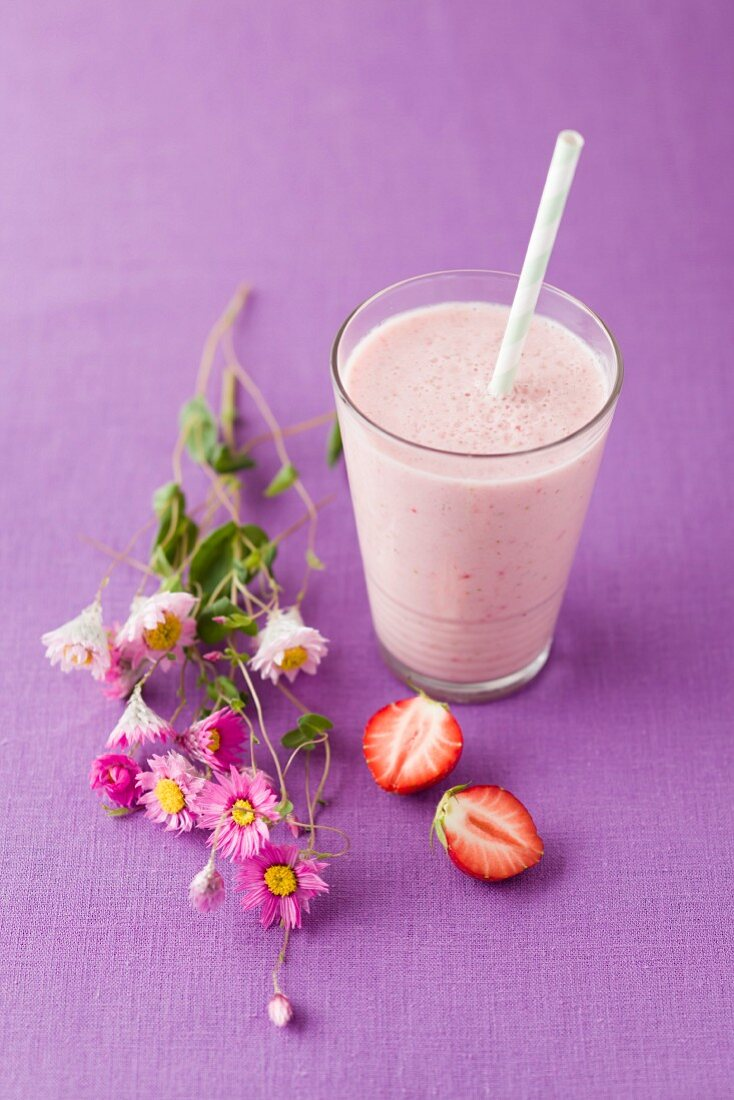 Glass of strawberry smoothie with cornflower blossom, close up