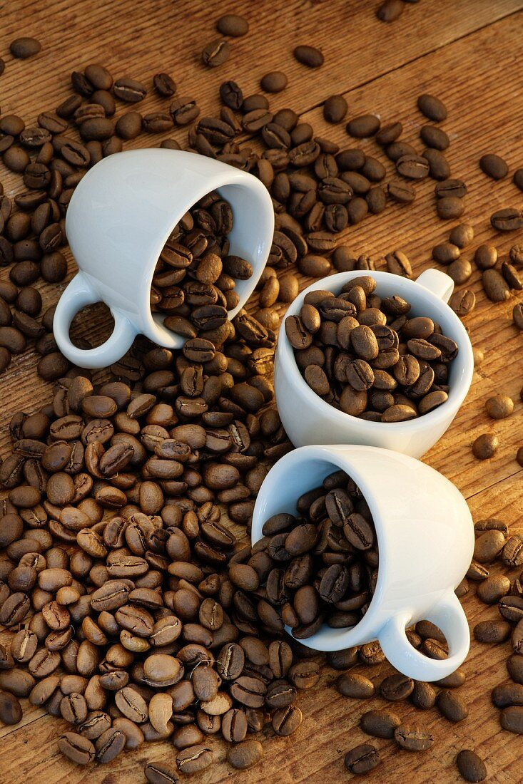 Still life with coffee beans and three espresso cups