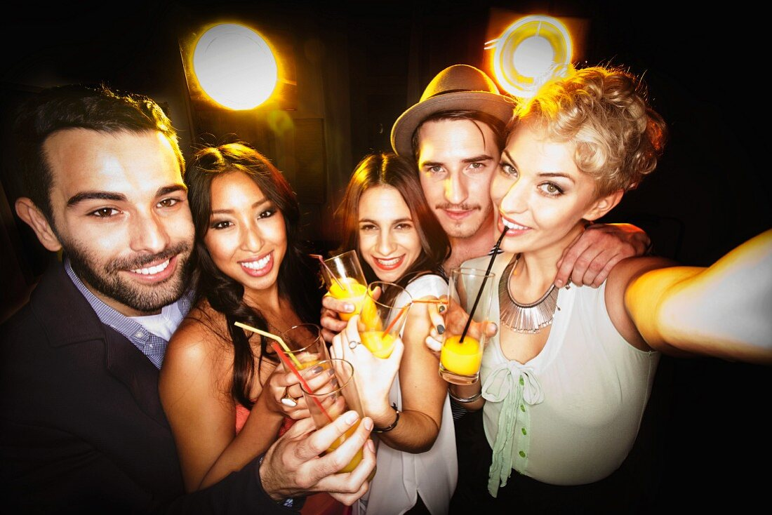 Smiling young people photograph themselves holding cocktails