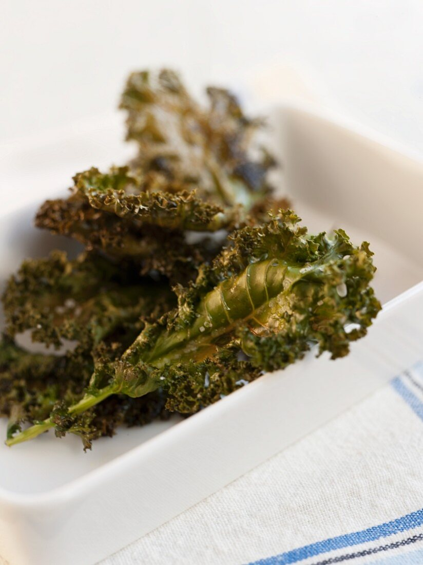 Baked Kale Chips with Sea Salt and Olive Oil in a White Dish